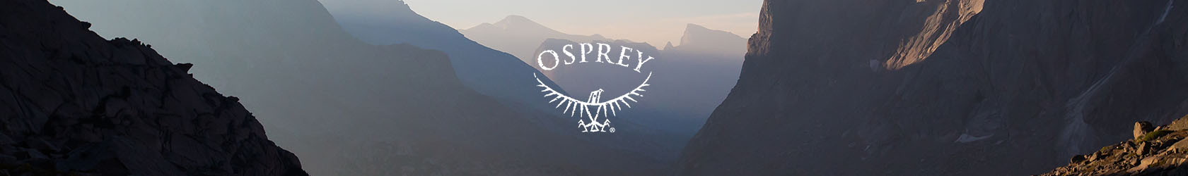 A couple with Osprey backpacks packing up after camping in rocky mountains